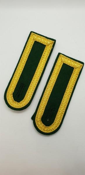 Schulterkappe, runde Form goldfarbig auf grünem Untergrund
